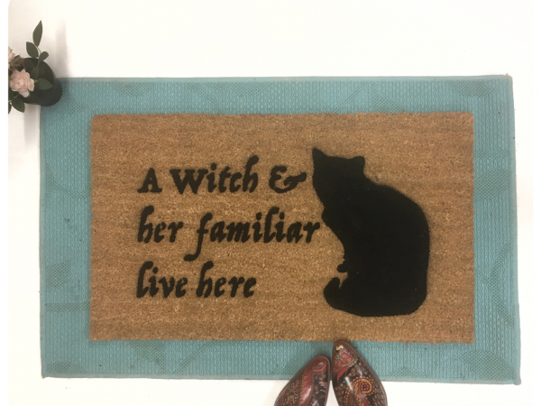 a witch and her familiar live here black cat halloween gothic home doormat